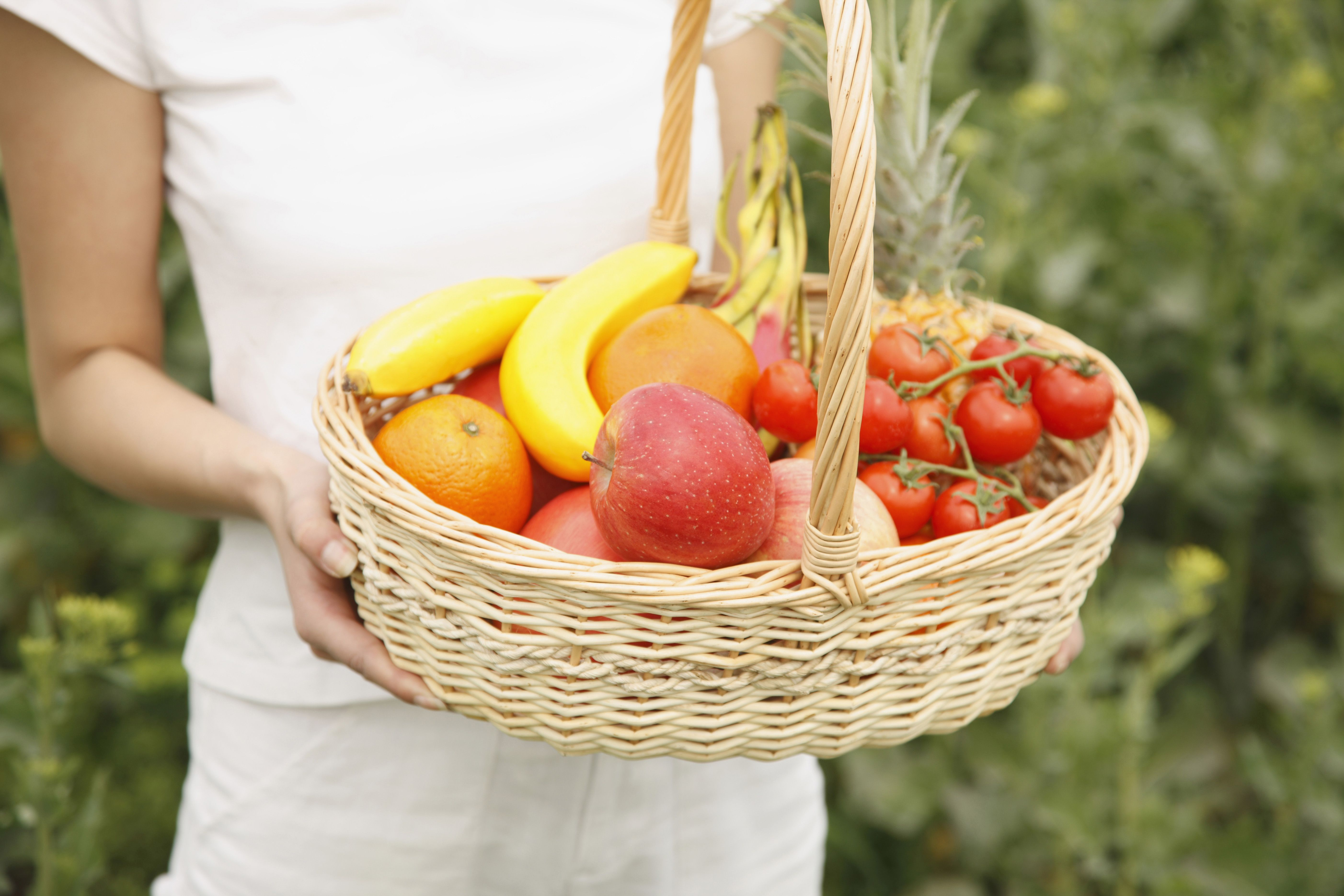 A woman in a white shirt and shorts carries a wicker basket with both hands. In the basket, there is an assortment of produce including oranges, apples, bananas, pineapples, and small tomatoes.
