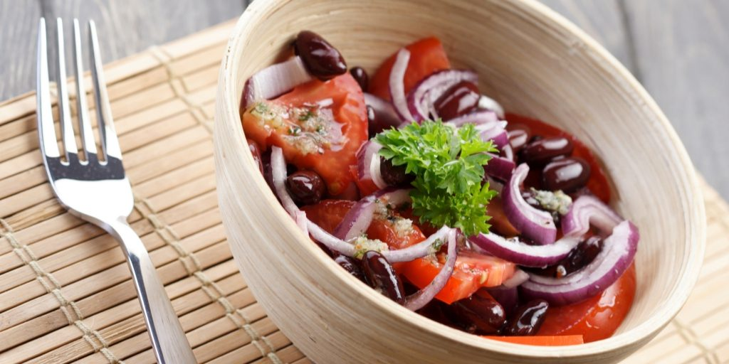 A beige bowl and a stainless steel fork rest on a bamboo mat. In the bowl, there are olives, slices of red onion, and large pieces of chopped tomato.