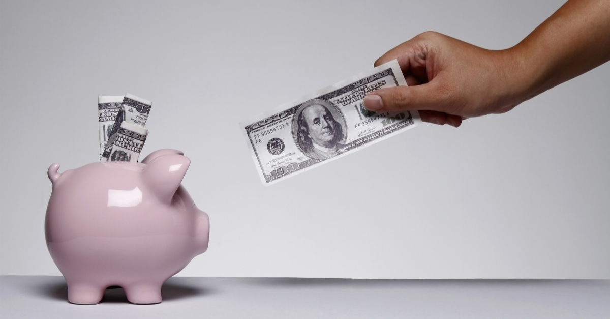 A pink piggy bank has three US 10-dollar bills sticking out of it. A brown hand holding a US 1-dollar bill reaches toward it.