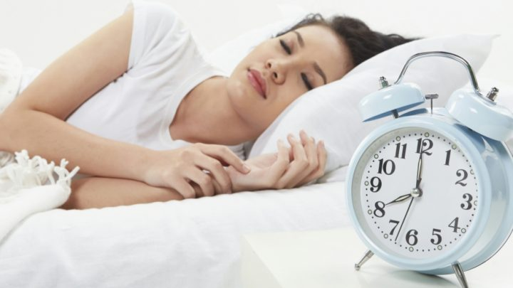 A woman in a white t-shirt is asleep on a bed with white sheets and a white pillow. A powder blue alarm clock is beside her on a white nightstand.