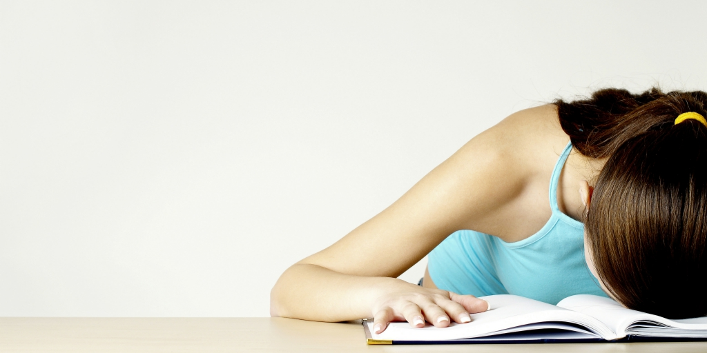 A girl in a blue tank top has her head down on an open book, which is resting on a table. The girl's hair is brown and tied into a low ponytail.