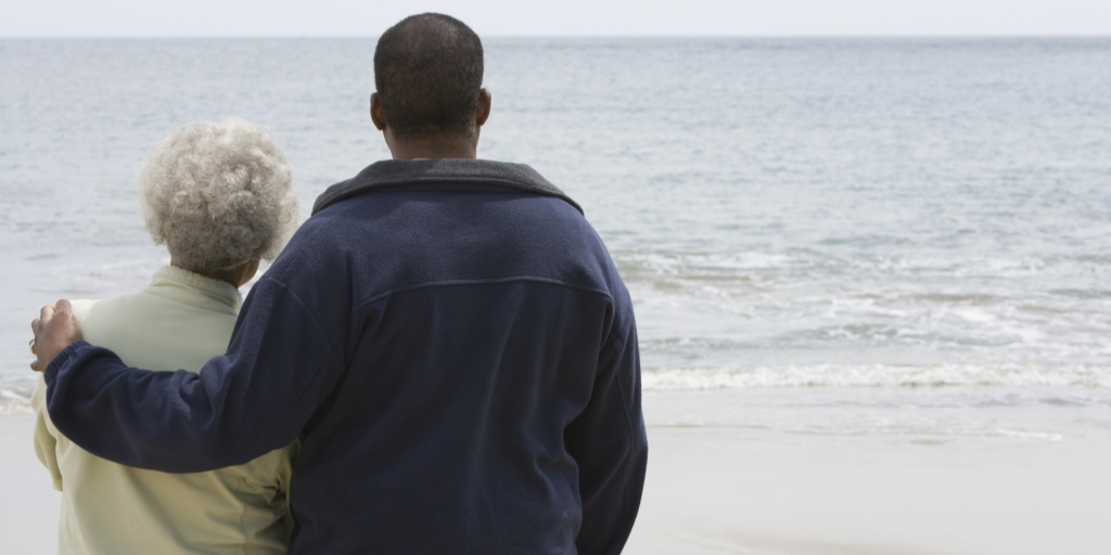 There are two people on the left side of the frame. They are standing with their backs facing the camera and staring out into a large body of water. The man (right) has his left arm around an older woman (left).