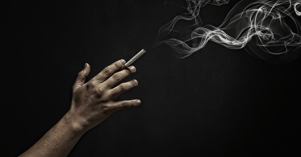 On a black background, a cigarette is being held between the first and middle fingers. A puff of smoke is visible in the top right corner.