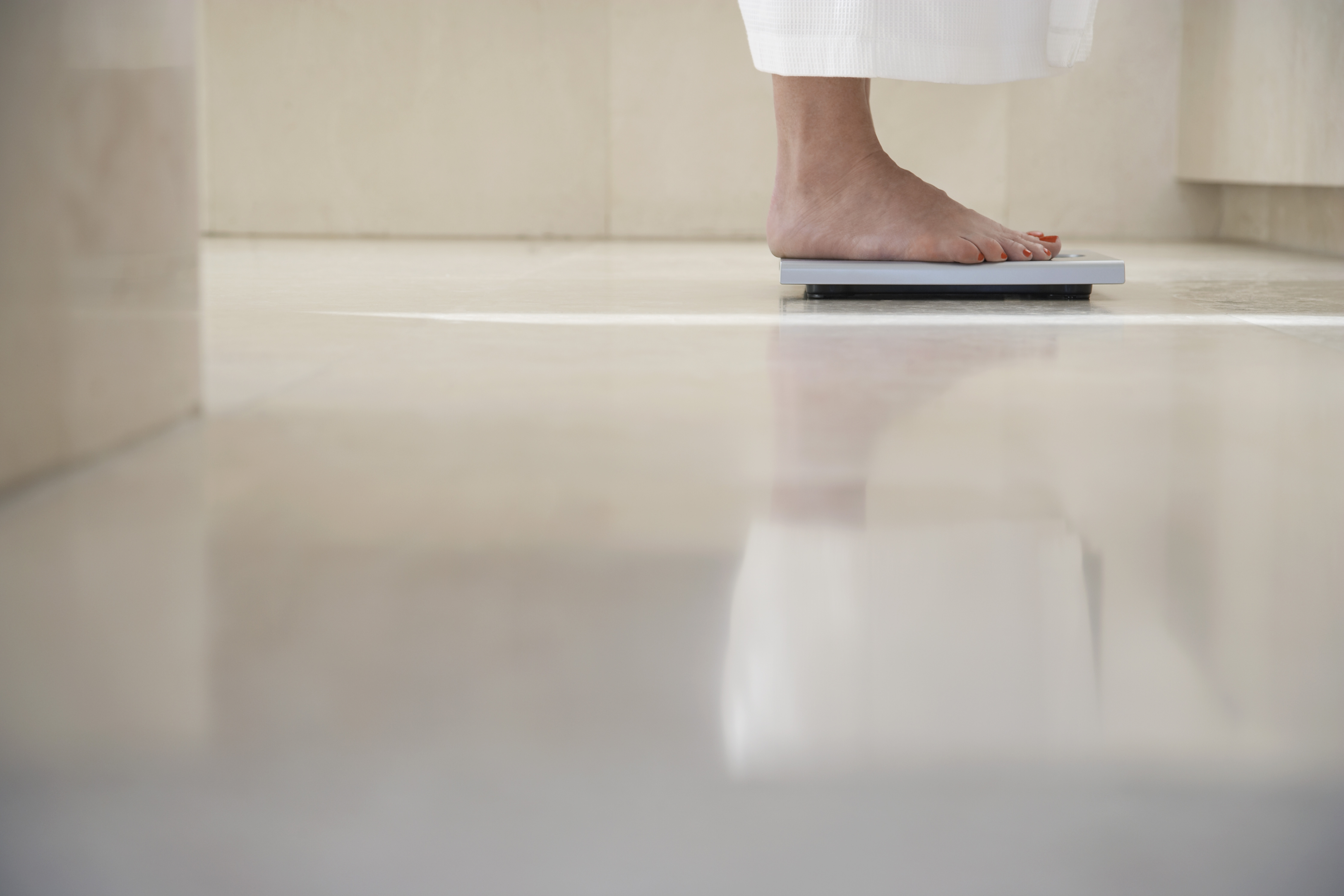 Woman on a bathroom scale. Only her feet are visible.