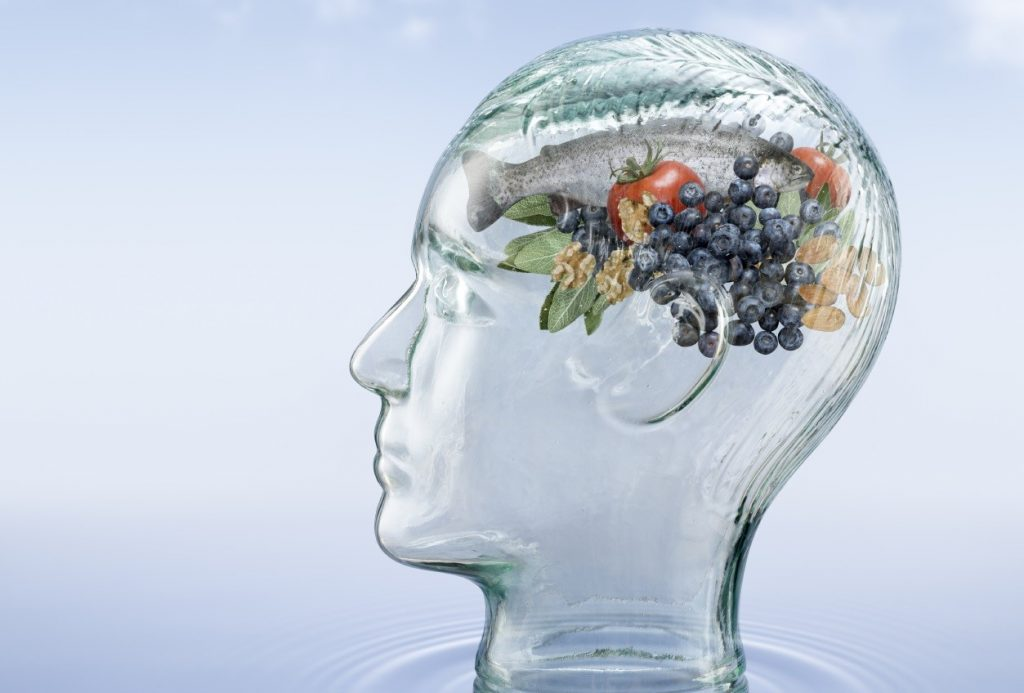 """Photo of a glass head on a blue background. The head's """"brain"""" is made up of different foods."""