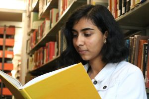 Harshini sitting in the library in front of bookstacks while reading a book