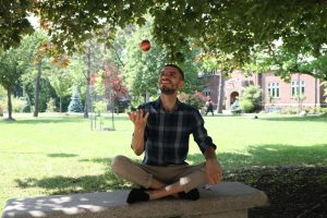 Wil sitting on an outdoor bench throwing a red apple in the air