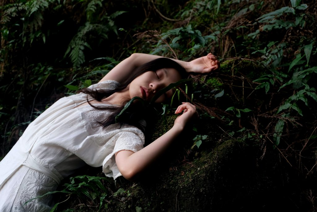 Person in white dress lying on a mossy rock with lush green trees all around them.