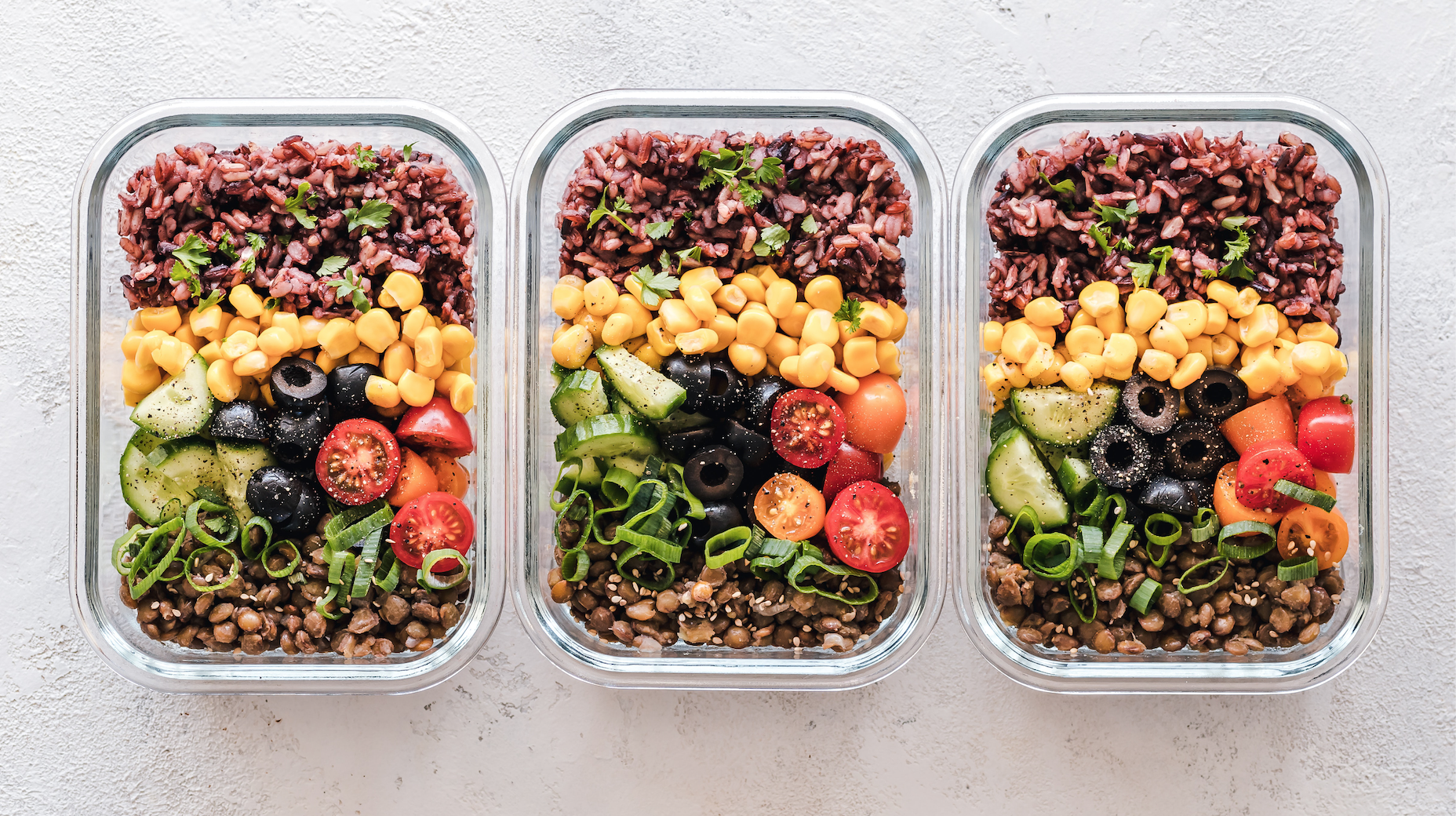 Three glass lock containers containing the same meal of brown rice, corn, cucumber slices, black olives, cherry tomatoes, green onion, and lentils.