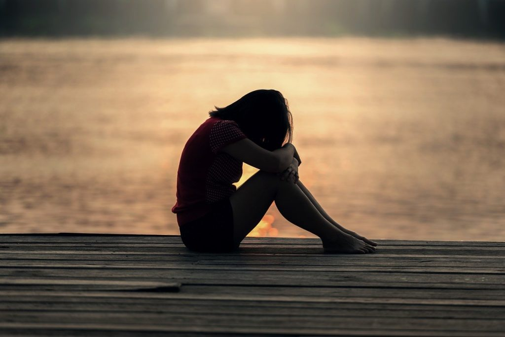 Sad girl sitting on deck with hands and arms clutching her knees.