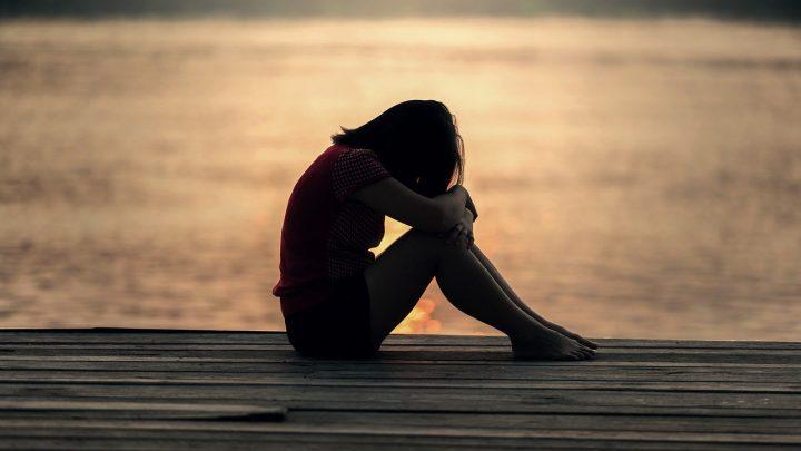 Sad girl sitting on deck