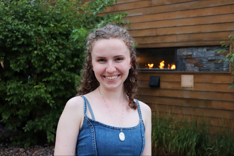 Summer smiling, outdoors, in front of a Milestone's restaurant.