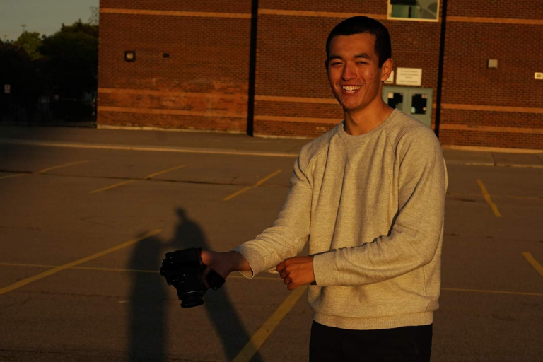 Connor smiling and holding a camera outdoors, with a building in the background.