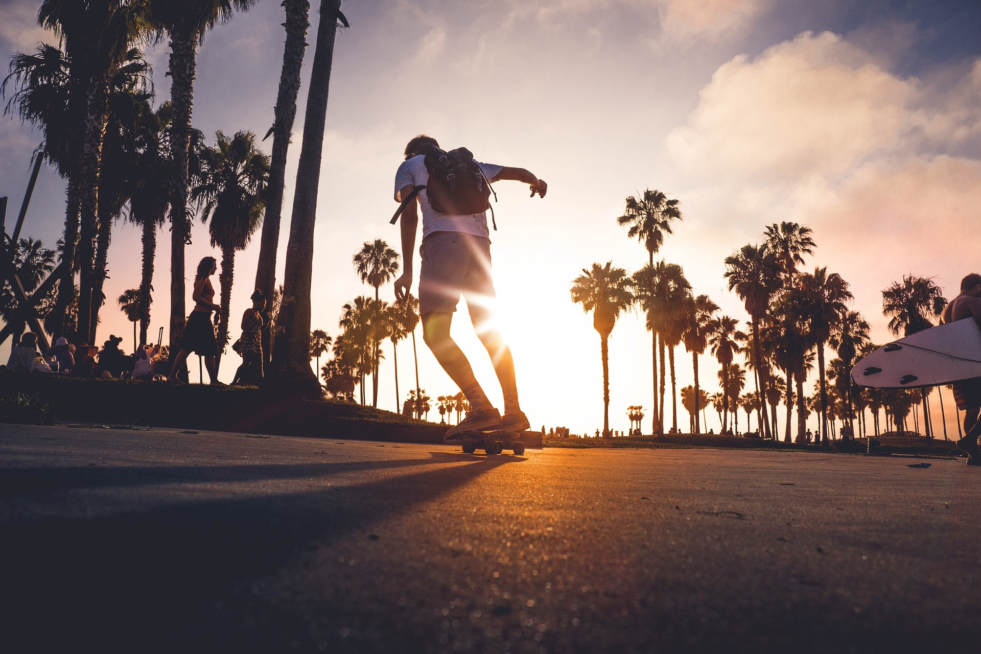Skateboarder with a backpack on a beachside road with palm trees in the background. Several other people in the background sitting or walking by.