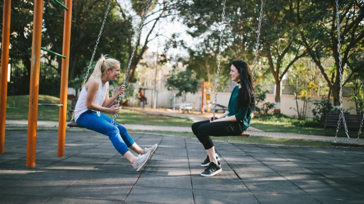 Two friends chatting while swinging on a swingset